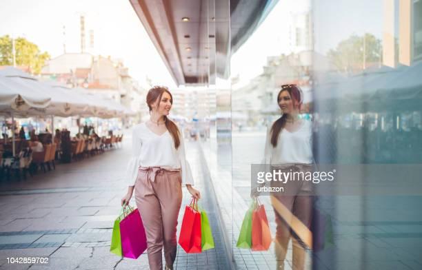 店の窓近くに歩いて買い物袋を持つファッショナブルな少女。