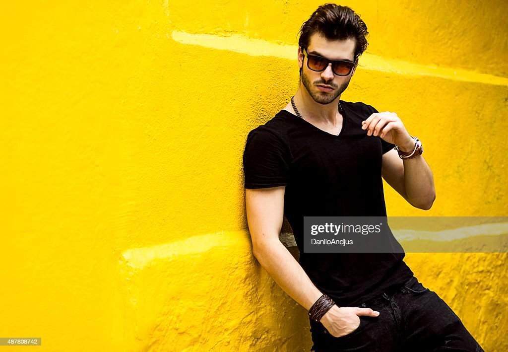 fashionable handsome man isolated on yellow wall : Stock Photo