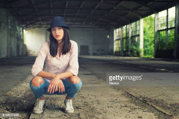 Fashionable hipster girl posing in abandoned building