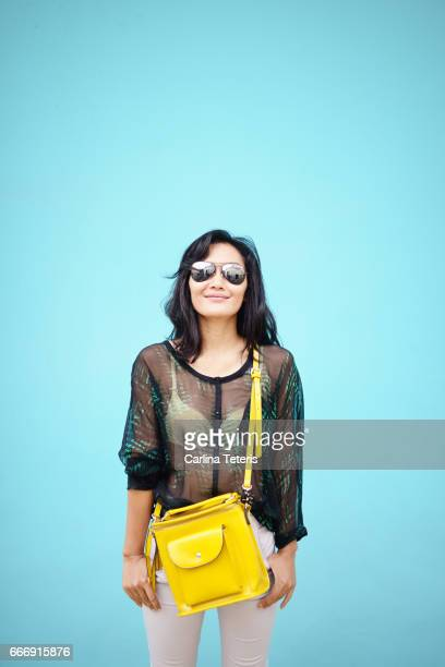 Fashionable Indonesian woman standing in front of a blue wall