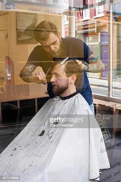 A fashionable man has a haircut in a barber shop on Brick Lane London UK