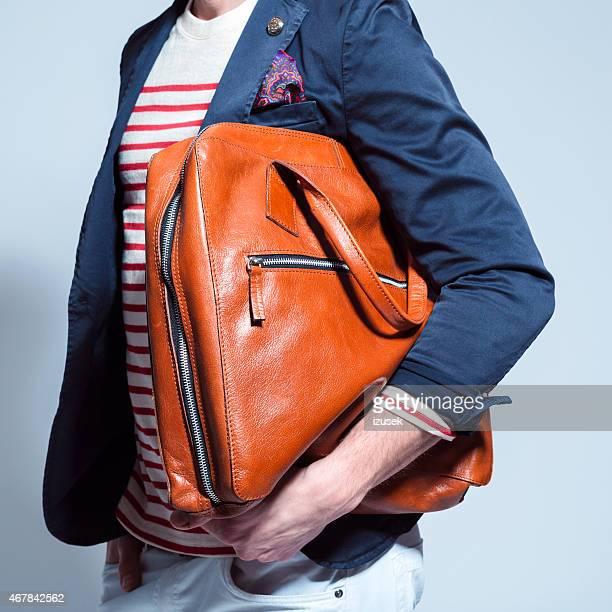 Fashionable man holding leather bag