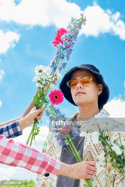 fashionable man poses with flowers - human limb stock pictures, royalty-free photos & images