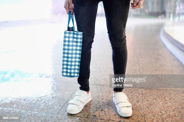 fashionable man's legs with shopping bag - enge jeans stock-fotos und bilder