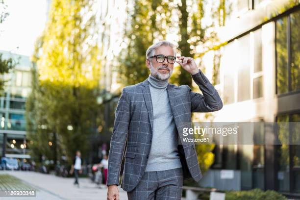 fashionable mature businessman on the go in the city - men fashion stock pictures, royalty-free photos & images