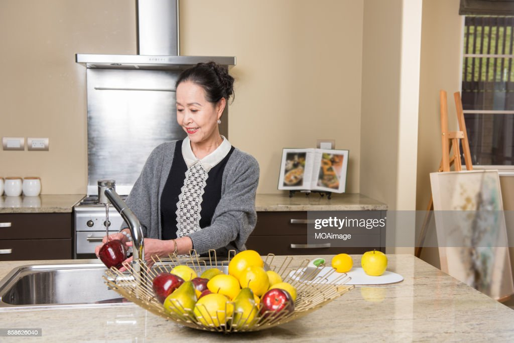 Fashionable mature woman in the modern kitchen : Stock-Foto