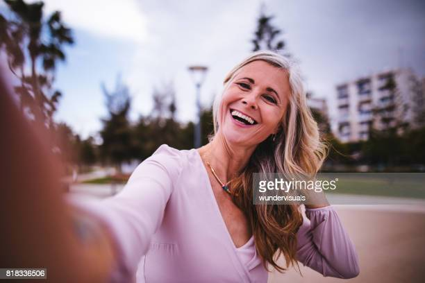 Fashionable mature woman posing in the city and taking selfies