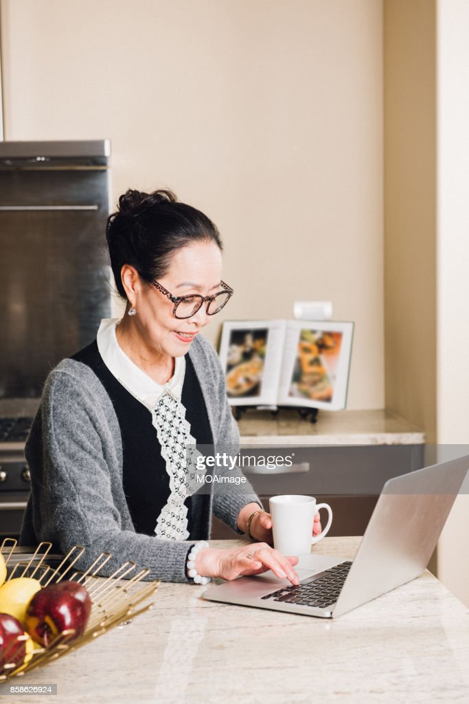 Fashionable mature woman using laptop : Stock-Foto