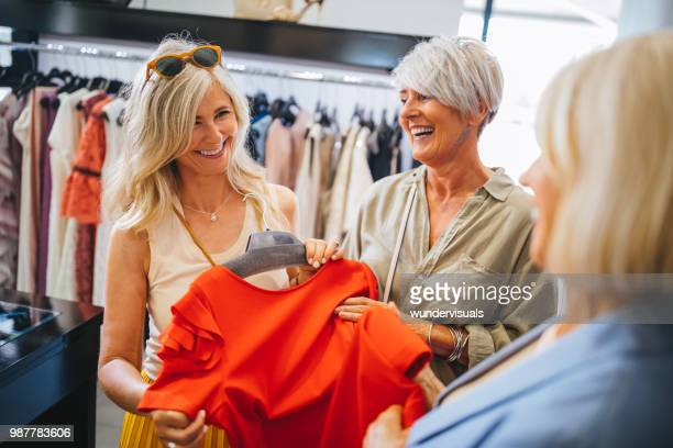 fashionable mature women shopping for clothes in fashion boutique - fashion stock pictures, royalty-free photos & images