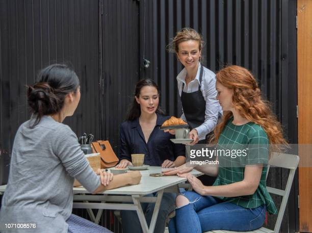 Fashionable modern women talking while enjoying coffee at a cafe together