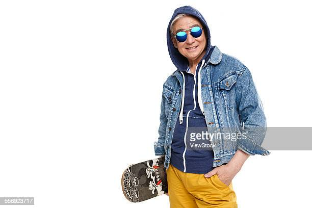 Fashionable old man holding a skateboard