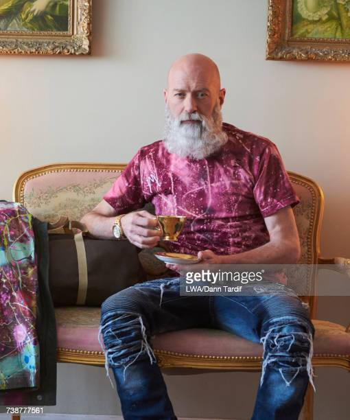Fashionable older Caucasian man with beard sitting on bench drinking tea