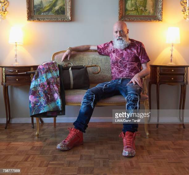Fashionable older Caucasian man with beard sitting on bench