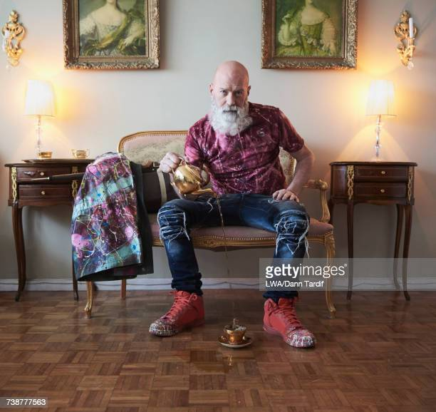 Fashionable older Caucasian man with beard sitting on bench pouring tea