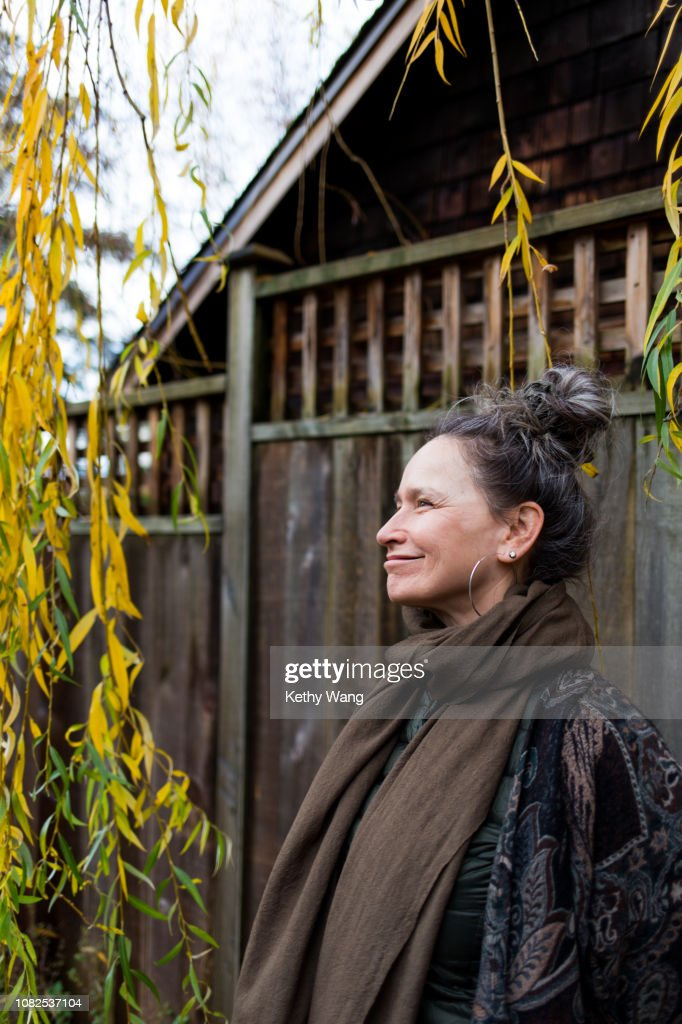 Fashionable older woman under a willow tree