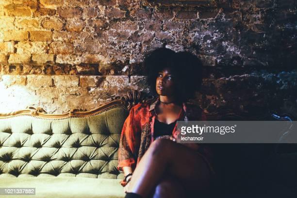portrait à la mode d'une belle jeune femme afro-américaine, reposante sur le sofa - parti politique photos et images de collection