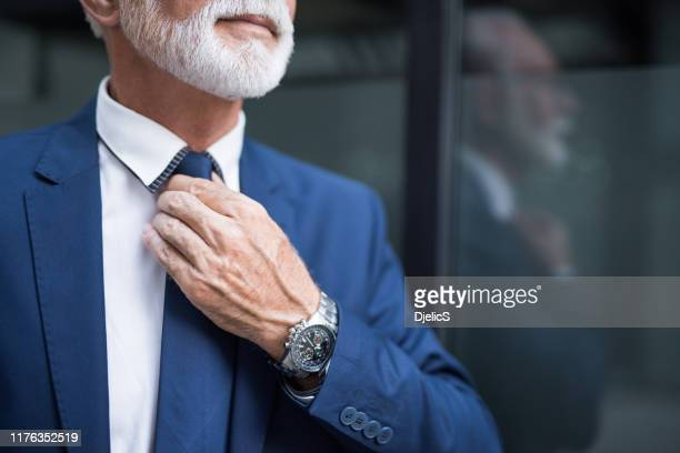 fashionable senior man adjusting a tie. - adjusting necktie stock pictures, royalty-free photos & images