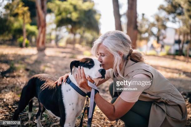 Fashionable senior woman kissing pet dog in nature