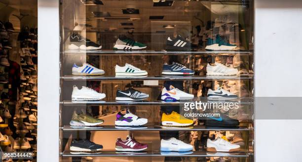 Fashionable sneakers on display in shop window, London, UK