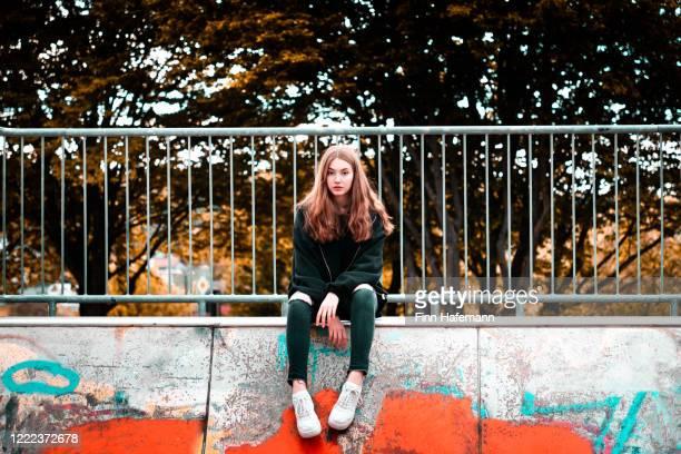 modische teenage girl sitzen auf urban concrete wall - jugendkultur stock-fotos und bilder
