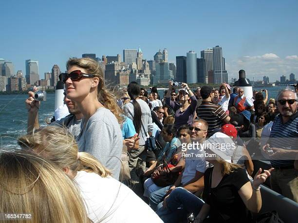 Fashionable tourists on the ferry to Liberty Island and the Statue of liberty in New York city. In the background is the skyline of Manhattan.