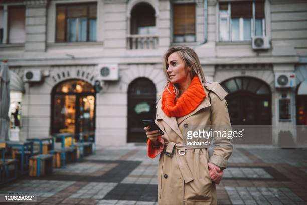 fashionable woman checking apps on her smartphone - trench coat stock pictures, royalty-free photos & images