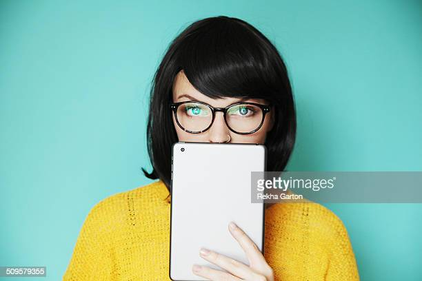 fashionable woman holding her tablet computer over her lips - rekha garton stock pictures, royalty-free photos & images