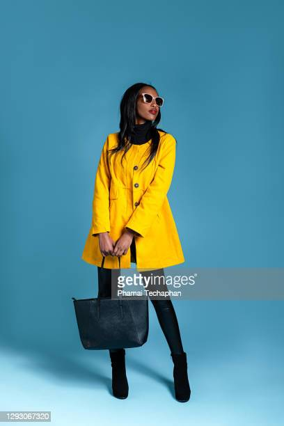 fashionable woman in a yellow coat - fashion model stock pictures, royalty-free photos & images