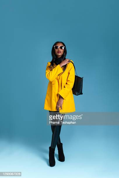 fashionable woman in a yellow coat - black purse stock pictures, royalty-free photos & images