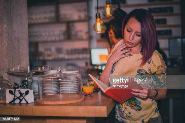 Fashionable woman ordering a drink at the bar