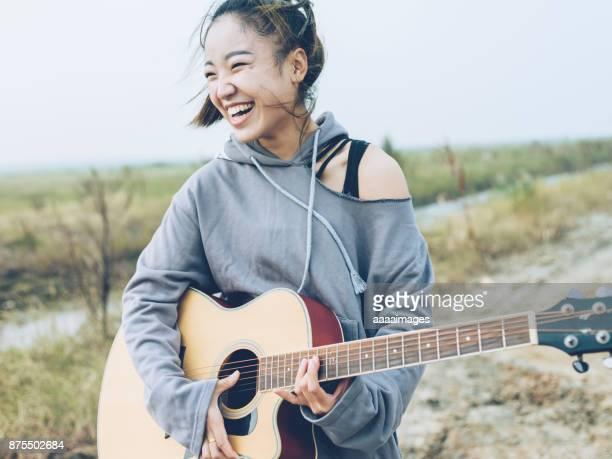 fashionable woman playing guitar on country road - paardenstaart haar naar achteren stockfoto's en -beelden