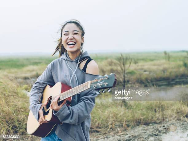 fashionable woman playing guitar on country road - chinese music stock pictures, royalty-free photos & images