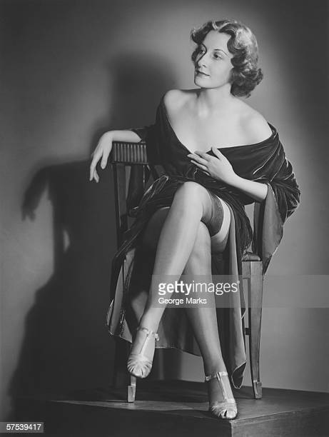 Fashionable woman posing in studio, showing legs, (B&W), portrait