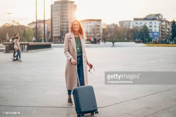 modieuze vrouw trekken koffer - mid adult men stockfoto's en -beelden