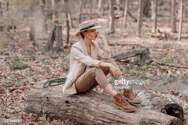 fashionable woman sitting on a log in the forest - beige shoe stock pictures, royalty-free photos & images