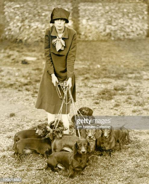 Fashionable woman stands on the grass holding nine datsuns on leashes, circa 1922.