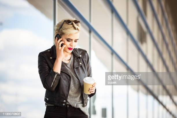 fashionable woman talking on phone at airport - izusek stock pictures, royalty-free photos & images