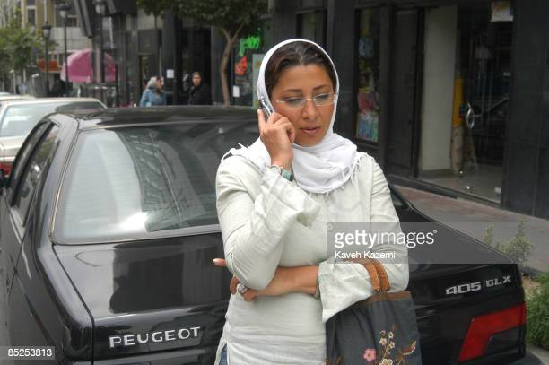 A fashionable woman talks on her mobile phone in a central Tehran street whilst leaning on a Peugeot 405 car assembled in Iran 10th July 2004
