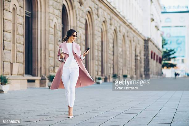 fashionable woman texting outdoors - weiblichkeit stock-fotos und bilder