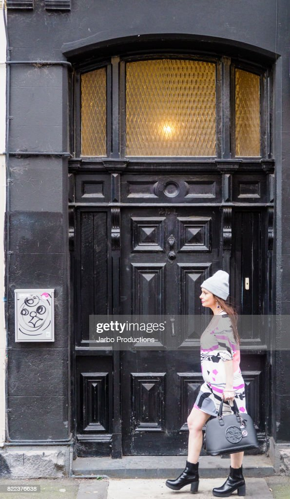 Fashionable Woman walks by a doorway in Fitzroy : Stock Photo