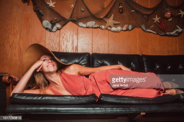 fashionable woman wearing jumpsuit, woman smiling, woman lying on side, woman wearing hat, woman relaxing, carefree woman - lying on side stock pictures, royalty-free photos & images
