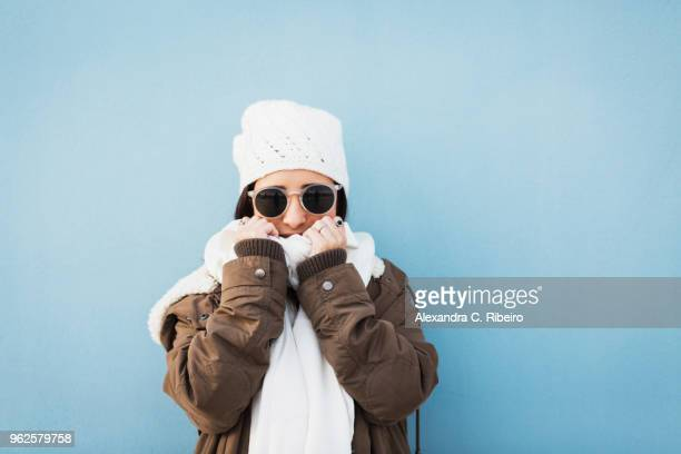 fashionable woman wearing warm clothing standing against blue background - abiti pesanti foto e immagini stock