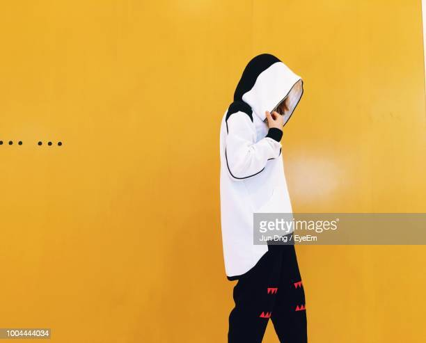 fashionable woman wearing white hooded shirt while walking against yellow wall - パーカー服 ストックフォトと画像