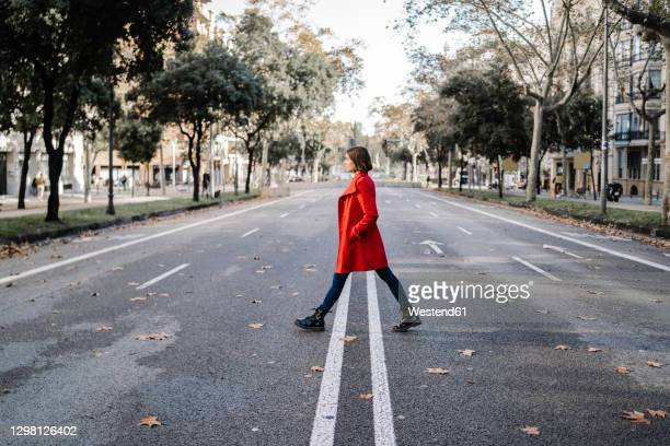 fashionable woman wearing winter jacket walking on road - jacket stock pictures, royalty-free photos & images
