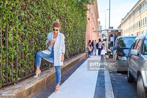 fashionable woman with a smartphone in the street, milan, italy - milan street style stock photos and pictures
