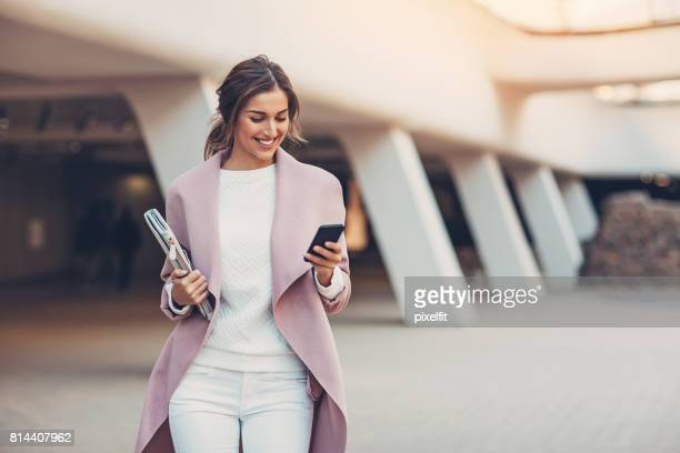 fashionable woman with smart phone - looking stock pictures, royalty-free photos & images