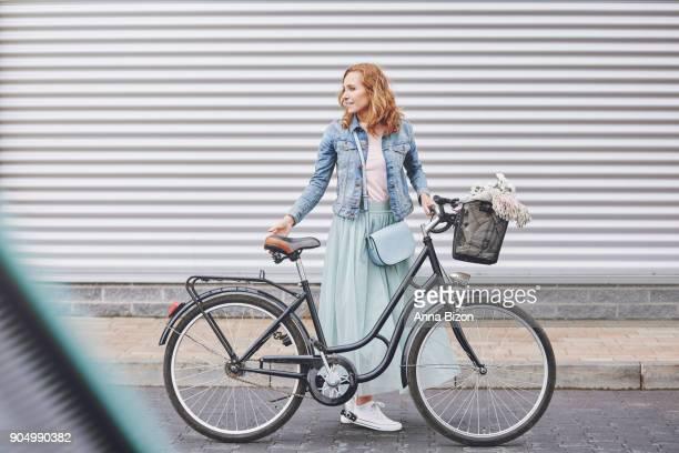 fashionable woman with urban bike in the city. debica, poland - rok stockfoto's en -beelden