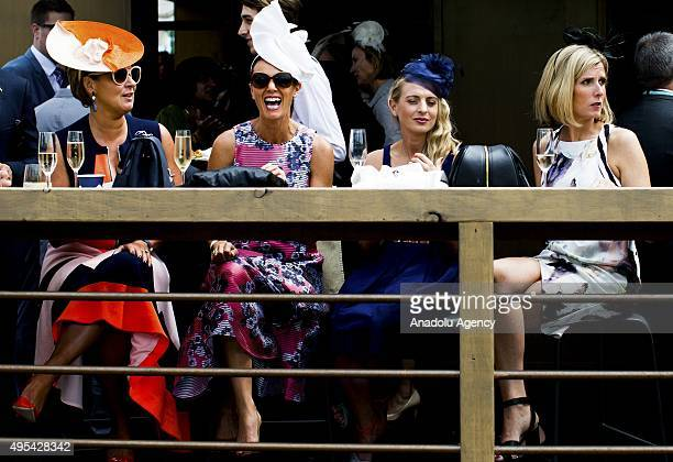 Fashionable women wearing headpieces share a laugh as they sit at a table of a marquee inside the birdcage during the 2015 Melbourne Cup Day at...