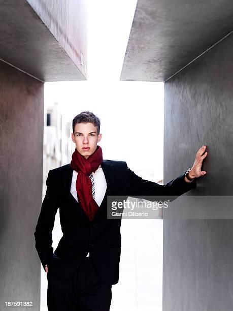 A fashionable young businessman posing between to walls