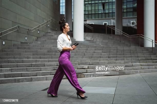 fashionable young businesswoman walking while holding diary in city - abbigliamento elegante foto e immagini stock